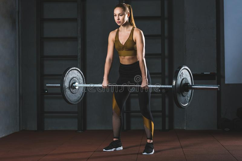 Front view of young sportswoman. Exercising with barbell in sports hall royalty free stock image