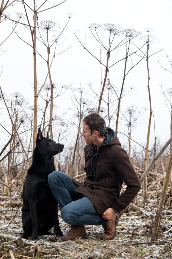 A man with a mongrel dog walking on a winter meadow royalty free stock photo