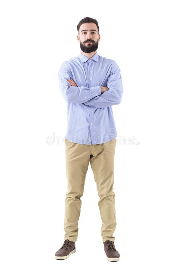 Front view of young successful bearded businessman with crossed arms looking at camera royalty free stock image