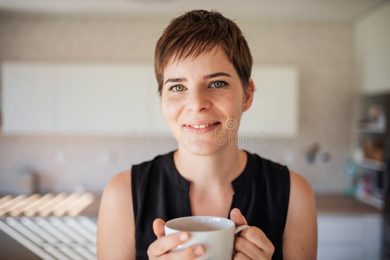 Front view of young woman with coffee standing indoors at home. royalty free stock photography