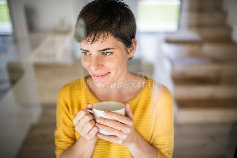 Front view of young woman with coffee standing indoors at home. royalty free stock images