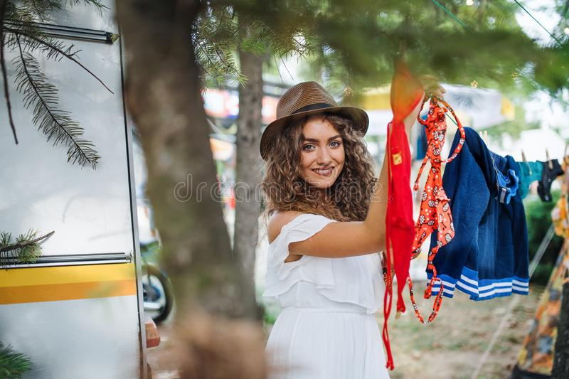 Young woman hanging towels at summer festival or camping holiday. stock images