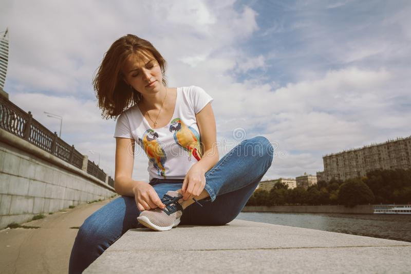 Front view of young woman tying shoe lace before run. Woman tying sport shoes sitting on the stone parapet near the river. portrait of pretty girl in blue royalty free stock images