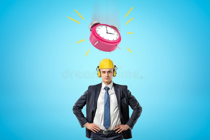 Front waist-deep image of businessman standing, hands on hips, wearing yellow hard hat with big pink alarm clock ringing royalty free stock photo