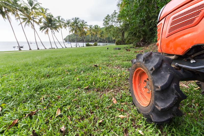 Close up of a wheel of a small tractor on the grass. royalty free stock images