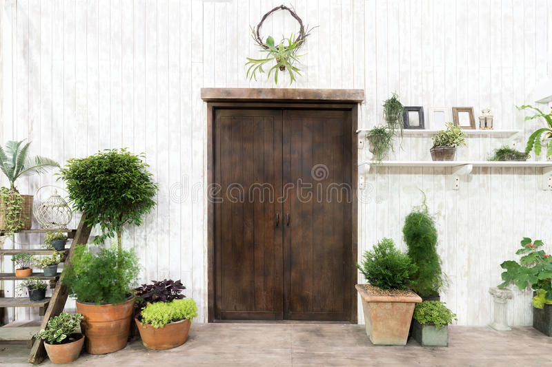 Front wood door and garden decor in white cosy house or cottage. Exterior of house stock image