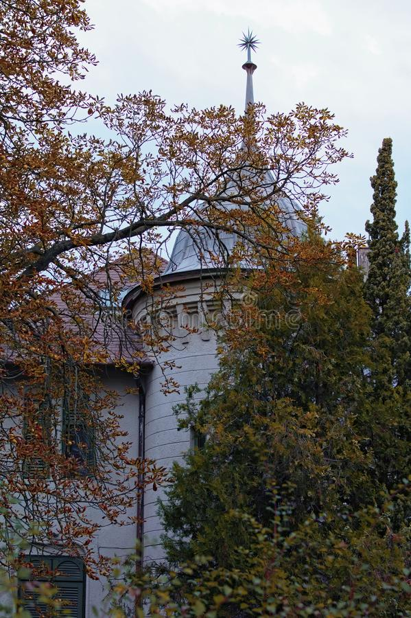 Front yard garden is hiding ancient house with the tower. Beautiful autumn landscape. Petofi Sandor street in Balatonfoldvar royalty free stock photography