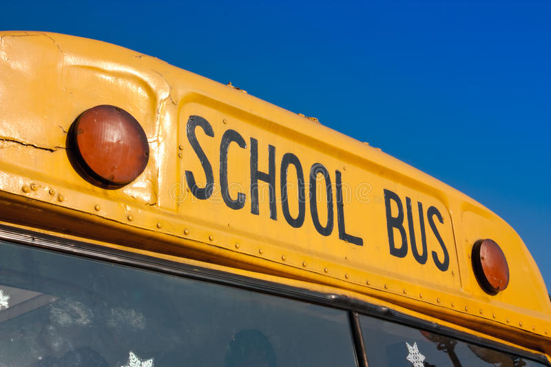 Front of yellow school bus. Against blue sky stock photography