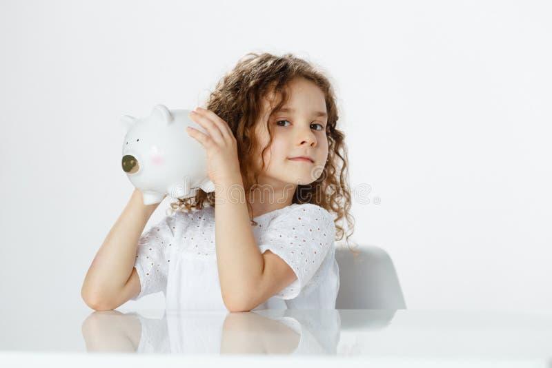 Frontaal portret die van een leuk krullend meisje in wit die een spaarvarken houden, omhoog haar oor houden om over witte achterg stock foto