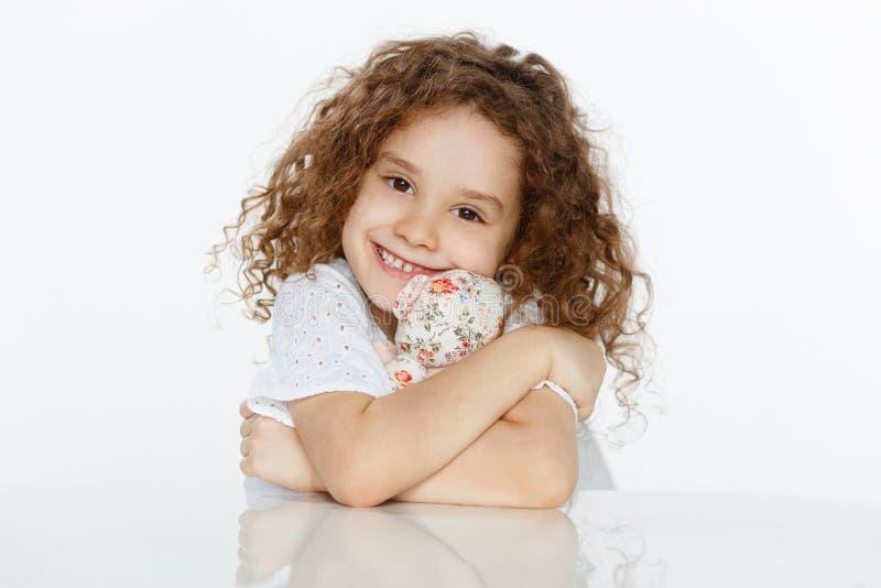 Frontaal portret die van vrolijk leuk krullend meisje een stuk speelgoed omhelzen, gezet bij lijst over witte achtergrond De ruim royalty-vrije stock foto's