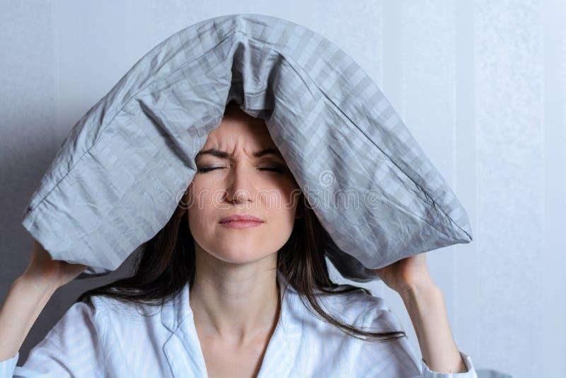 Frontaal portret van een eenzame vermoeide vrouw met een hoofdkussen op haar hoofd die aan slapeloosheid lijden Lawaaierige buren royalty-vrije stock afbeelding