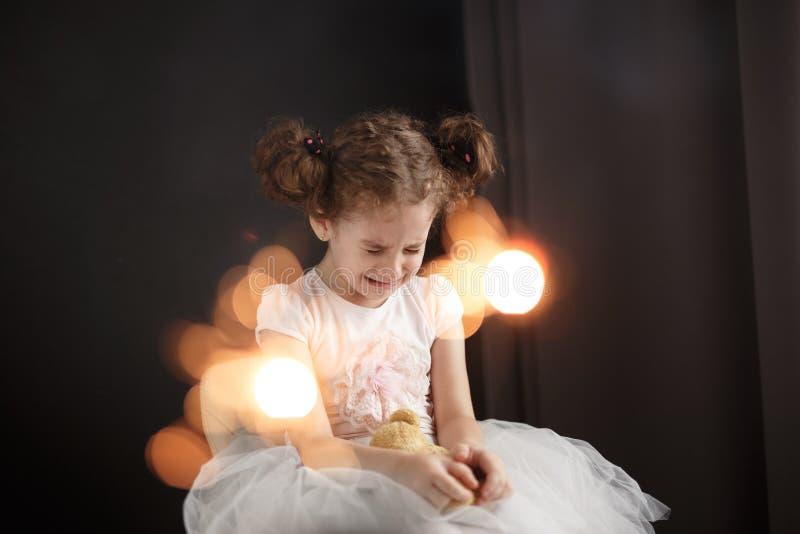 Frontaal portret van een ongelukkig klein schreeuwend krullend meisje Droevige die verjaardag, op een donkere achtergrond wordt g stock afbeeldingen