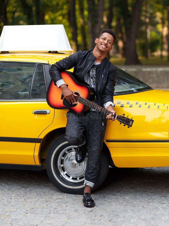 Frontaal portret van vrolijke moderne veelvoudige raskerel in vrijetijdskleding dichtbij gele uitstekende auto, spel bij gitaar b stock foto