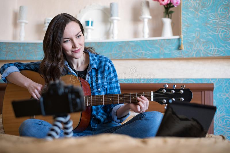 Frontal horizontal image of a pretty woman on the bed in the bedroom, records a music blog and plays acoustic guitar.  stock images