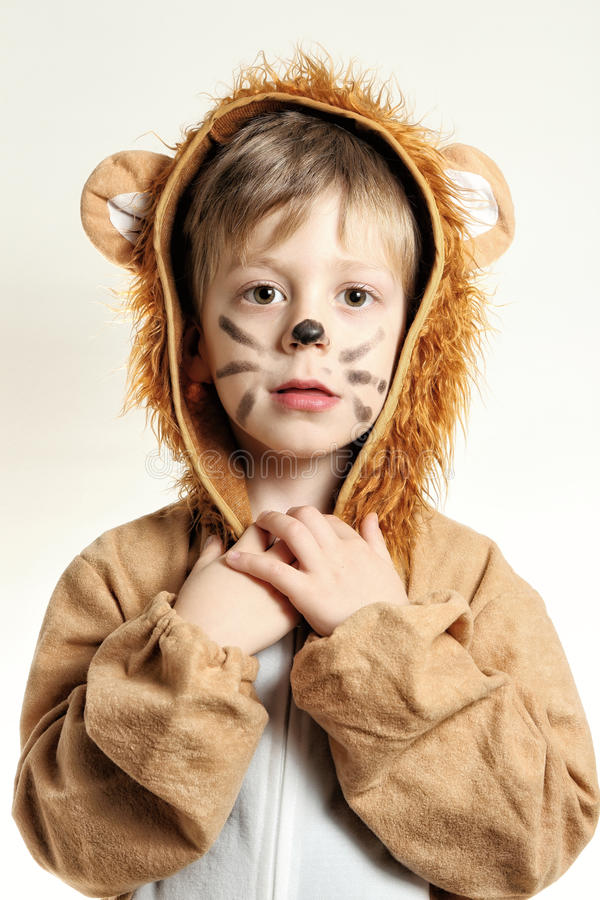 Frontal portrait of the boy dressed for lion with whiskers. Portrait of boy in lion dress holding his neck stock photo