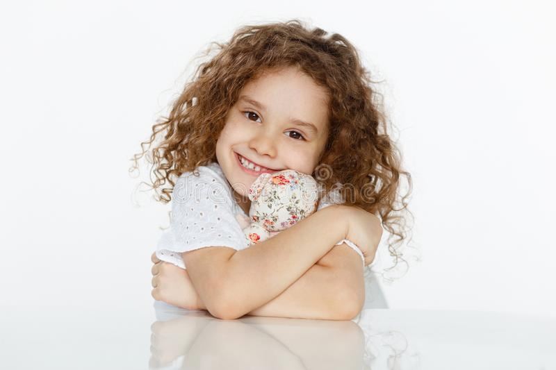 Frontal portrait of cheerful cute curly little girl embracing a toy, seated at table over white background. Copy space royalty free stock photos