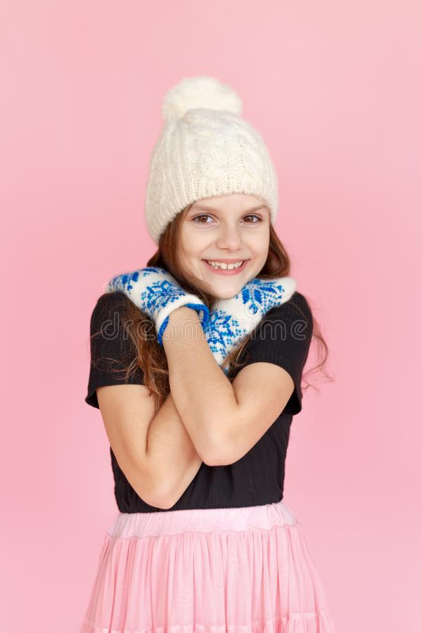 Portrait little girl in warm knitted white hat and mittens, he embraced with his hands, on pink background in studio. royalty free stock images