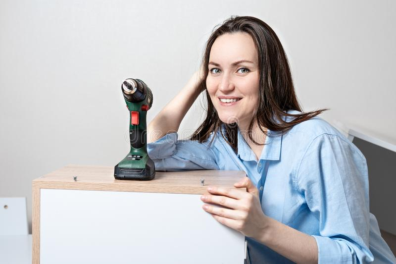 Frontal portrait of young smiling European woman with electric screwdriver leaning on the assembled table stock photo