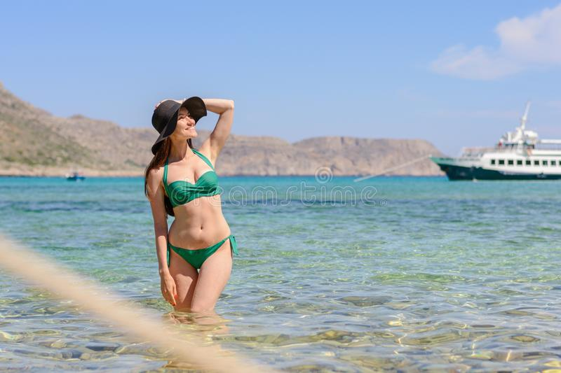 Frontal portrait of a young woman brunette in a green swimsuit standing in the emerald sea water and a hand holding a hat, copy sp royalty free stock photography