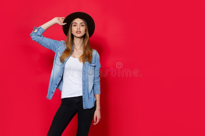 Frontal portrait young woman in hat and denim, looking at camera, isolated on a red background, with copy space. stock image