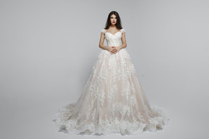 Frontal sikt av en fantastisk kvinnlig modell i wendding klänning för lång prinsessa som isoleras på en vit bakgrund royaltyfri bild