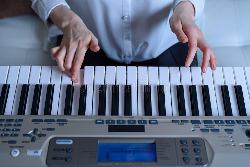 Frontal sikt av en kvinna som lär att spela det elektroniska pianot arkivbilder