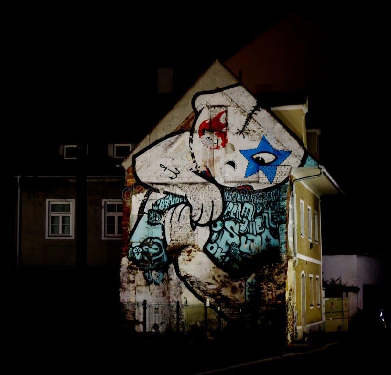 Frontal sikt av ett stads- hus med en massiv grafitti på fasaden i en storstad på natten royaltyfri bild