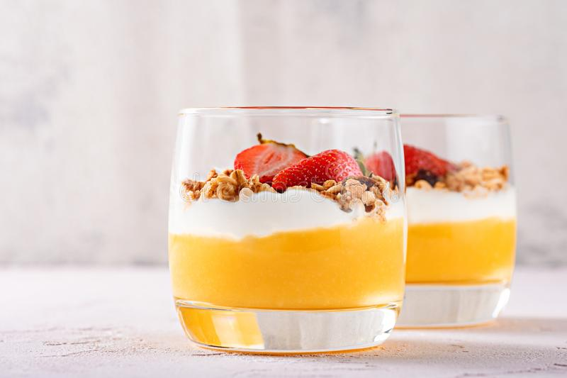 Frontal two glasses with dessert Panna cotta from mango smoothie, ricotta, mussels and strawberry pieces stock image