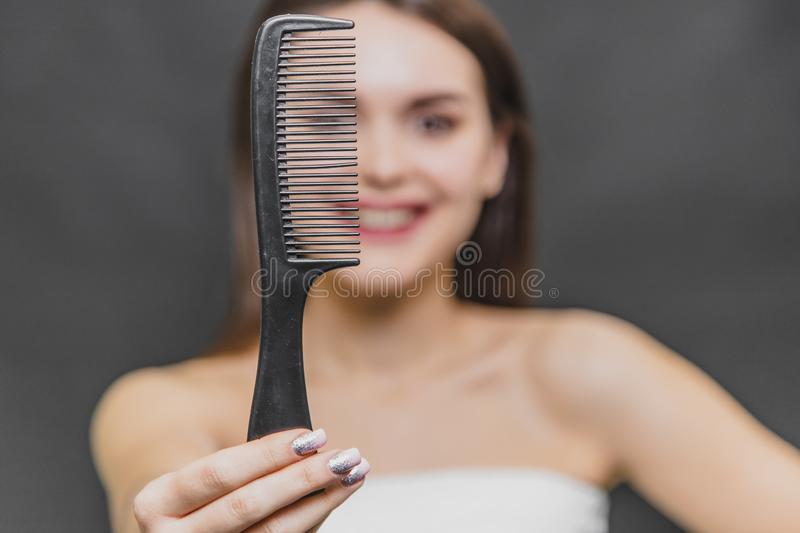 Frontal view of a beautiful young girl in a white razor. Combing hair. Close-up of a comb on a girl`s blurry background. royalty free stock photo