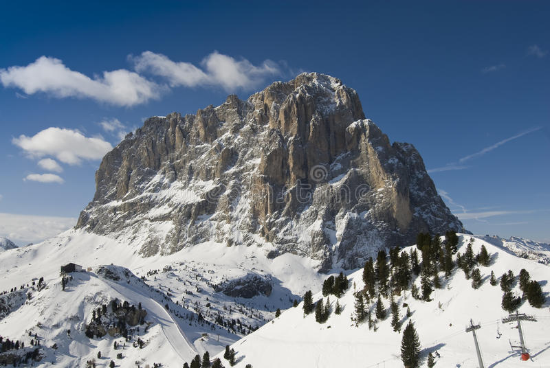 Frontal view of a mountain peak in winter. Frontal view of the Sassolungo mountain peak in winter with blue sky. Val Gardena, Dolomites, Italy royalty free stock images