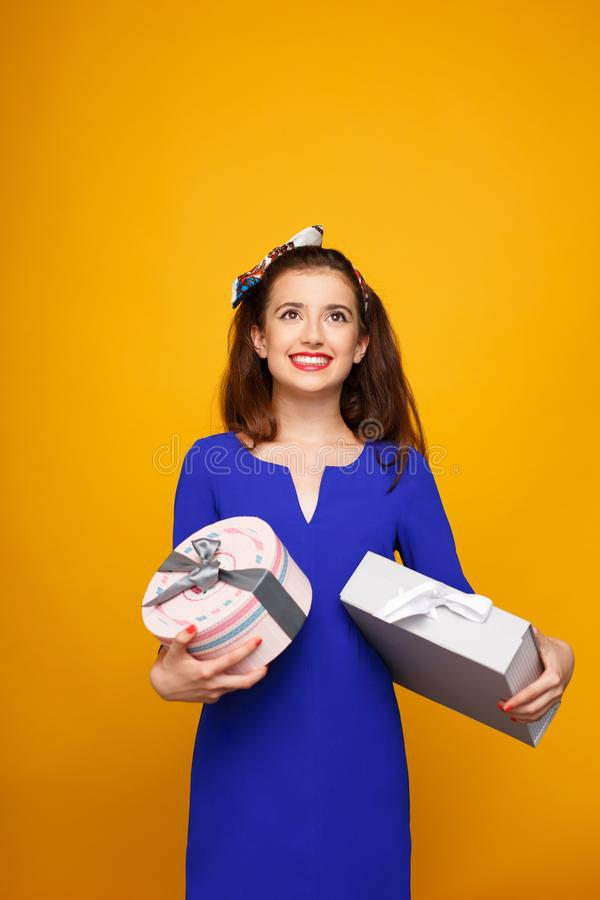 Cheerful girl in blue dress holding heap of presents, looking up,  on yellow background. Copy space. stock photography