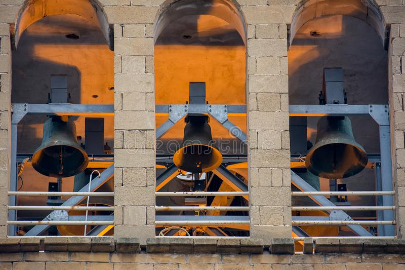 Frontal View Of Three Church Bells. On Golden And Blue Lights Background royalty free stock photography