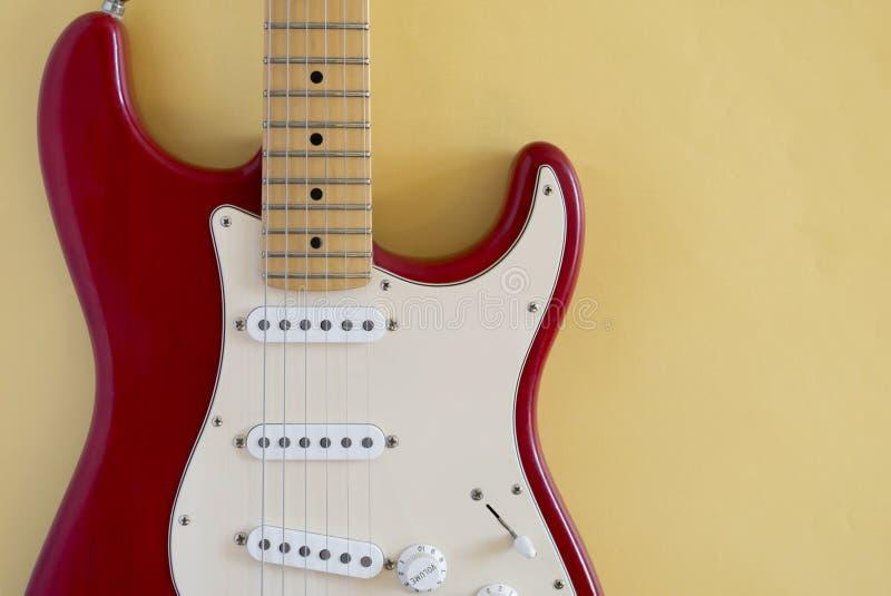 Frontales Bild einer E-Gitarre auf einem gelben Hintergrund stockfotografie