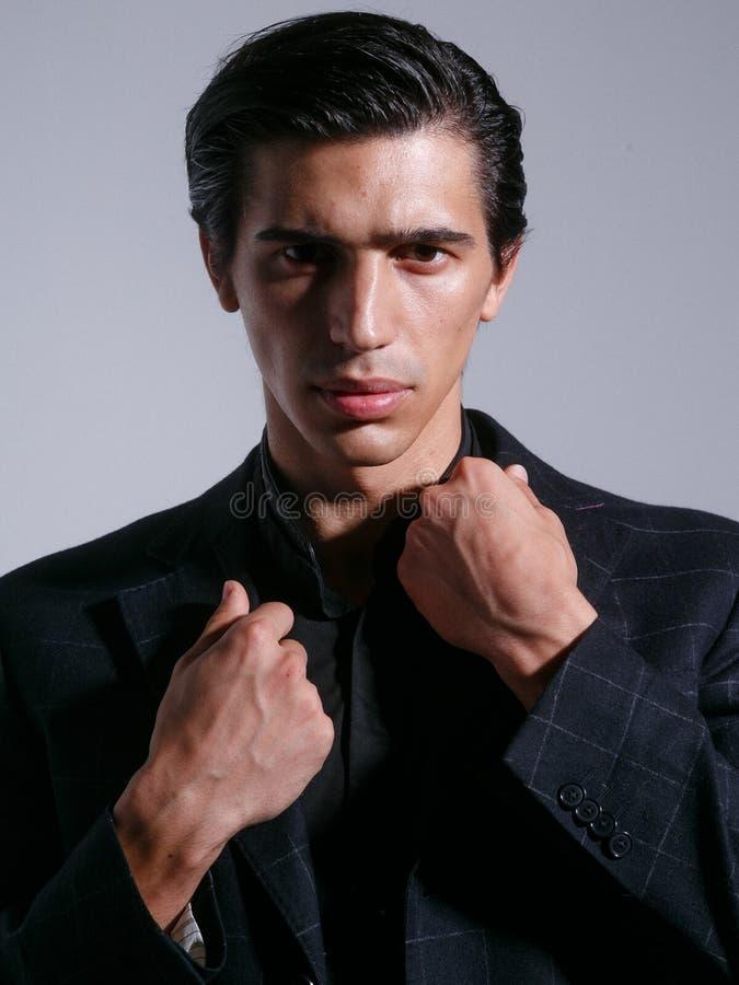 Frontales Porträt des überzeugten Mannes im schwarzen Anzug, wirft mit attitudine im Studio auf, lokalisiert auf weißem Hintergru lizenzfreie stockfotos
