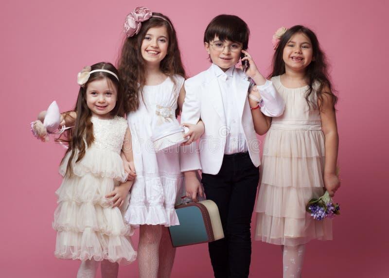 Frontales Porträt einer Gruppe glücklicher Kinder gekleidet in der schönen klassischen Kleidung, lokalisiert auf rosa Hintergrund lizenzfreies stockfoto