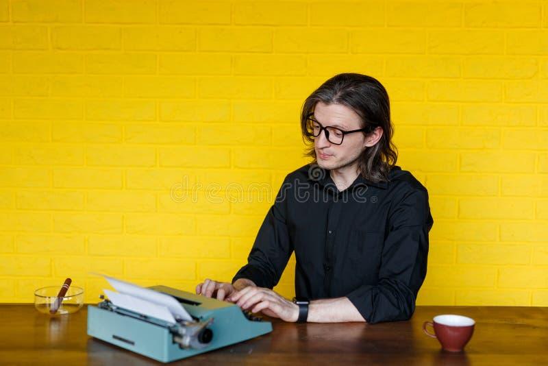 Frontales Porträt eines Mannes im schwarzen Hemd, gesetzt auf einer Tabelle, arbeitend an einer Schreibmaschine, über gelber Wand lizenzfreie stockfotografie