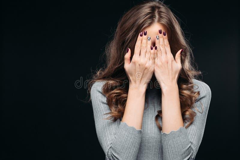 Fronte adorabile stupito della copertura della donna con la mano fotografia stock