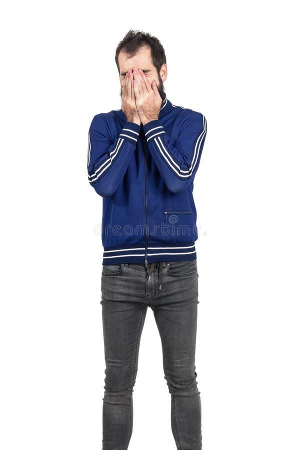 Fronte barbuto della copertura del giovane con la sua risata delle mani fotografia stock