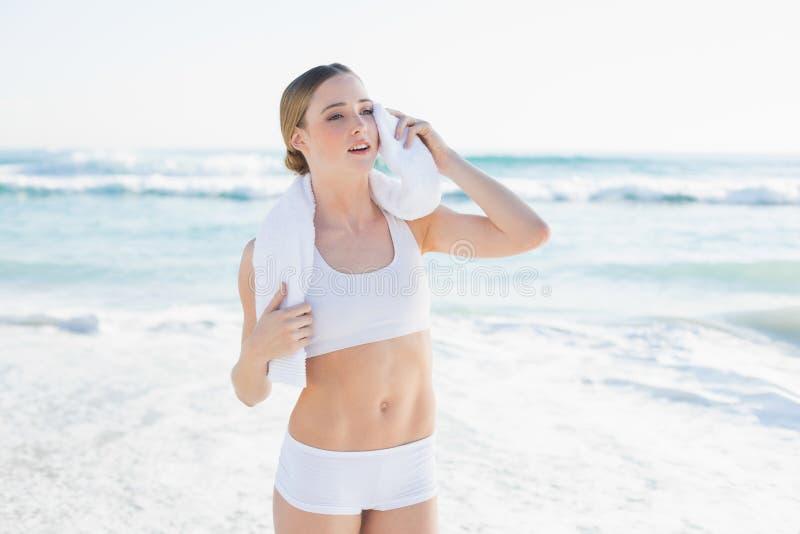 Fronte commovente aggrottante le sopracciglia della donna snella con l'asciugamano bianco immagini stock libere da diritti