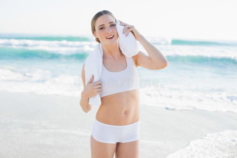 Fronte commovente sorridente della donna snella con l'asciugamano bianco immagini stock