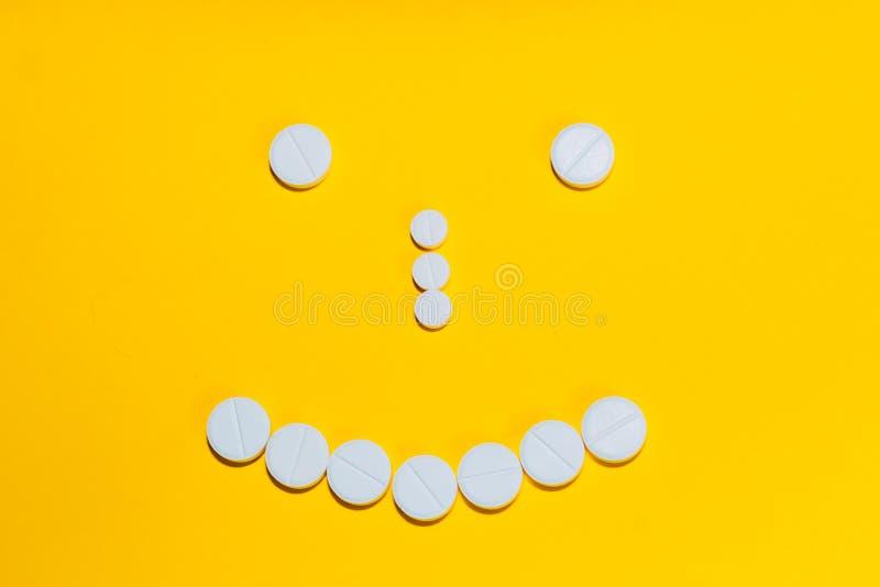 Fronte con un sorriso presentato con le pillole e le vitamine su un fondo giallo fotografia stock libera da diritti