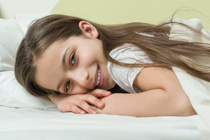 Fronte del primo piano di bella bambina sorridente che si trova a letto su un cuscino fotografia stock