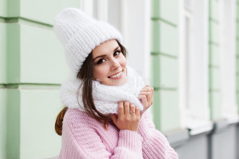 Fronte del primo piano di giovane donna sorridente che gode dell'inverno che porta sciarpa e cappello tricottati immagine stock