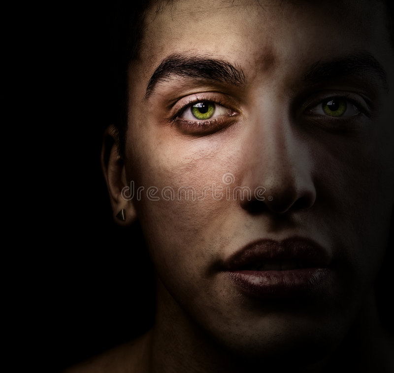 Fronte dell'uomo nello scuro con i bei occhi verdi fotografie stock libere da diritti