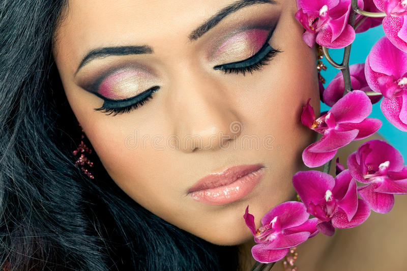 Fronte della bella donna con i fiori dell'orchidea fotografia stock libera da diritti
