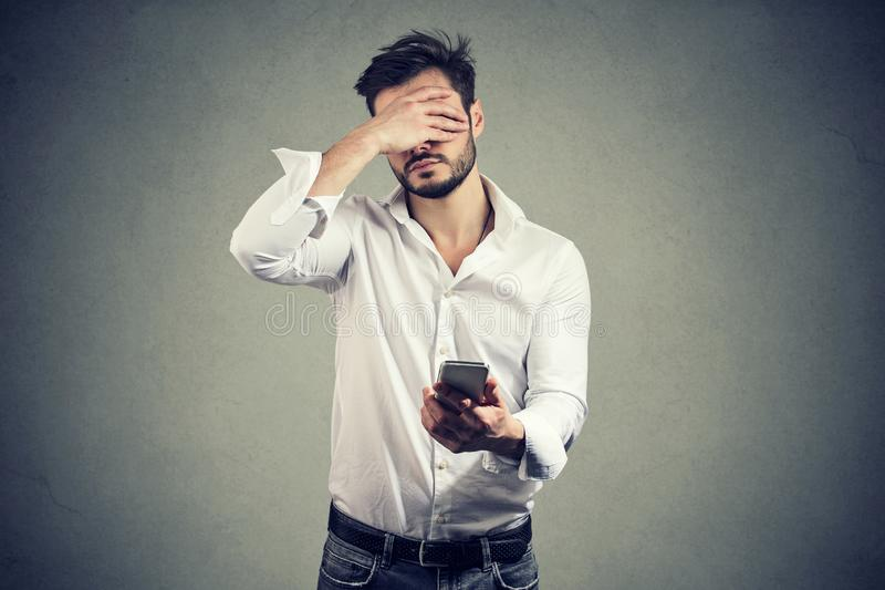Fronte della copertura dell'uomo nella disperazione che ha cattive notizie sullo smartphone contro fondo grigio fotografia stock