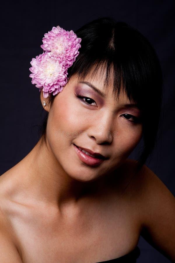 Fronte della donna asiatica con i fiori fotografie stock