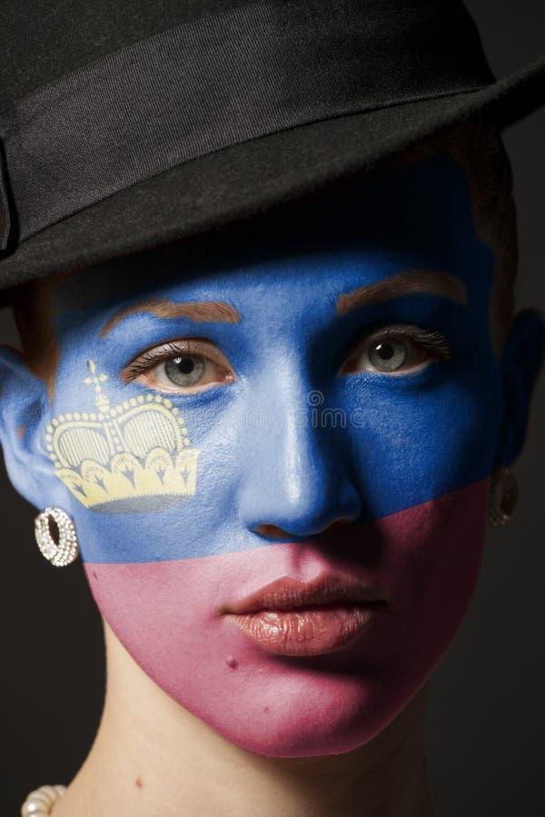 Fronte della donna con la bandiera dipinta del Liechtenstein immagine stock