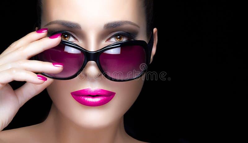 Fronte della donna del primo piano in occhiali da sole surdimensionati rosa Trucco e Mani fotografie stock libere da diritti