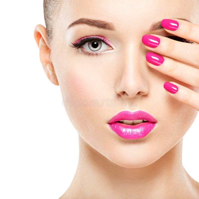 Fronte della donna di Eautiful con trucco rosa degli occhi e dei chiodi fotografie stock libere da diritti